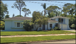 While most late-1940s Bahama Shores ranch-style homes were one story, a few had a second story, usually a single room with bath as is the case here over the garage. Note the simple horizontal detailing on the exterior wall and chimney (partially obscured by the tree), the use of spiral grill work for the balcony, and the tailings on either side of the home making the structure appear larger. This may have been the first home built as a part of the Bahama Shores development and used as a model home.