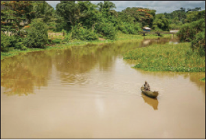 cene of Dugout Canoe with villager on river that divides Oloibiri Island from Mainland
