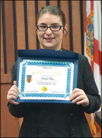 Deanna Foster proudly showing her CNA certificate