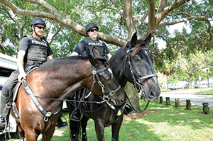 Officer Ron Try and his four-legged partner Brooklyn, and Officer Jason Hughes and his equine partner Jacob