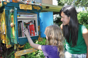 A Japanese exchange student is introduced to Robin's uniquely decorated Little Free Library Box by a neighbor child.