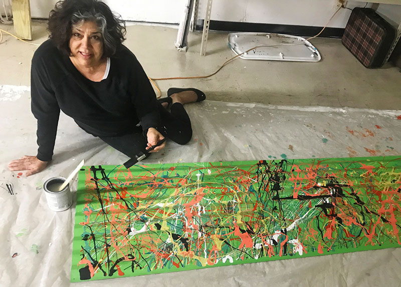 Michelle puts the finishing touch on a wall painting.